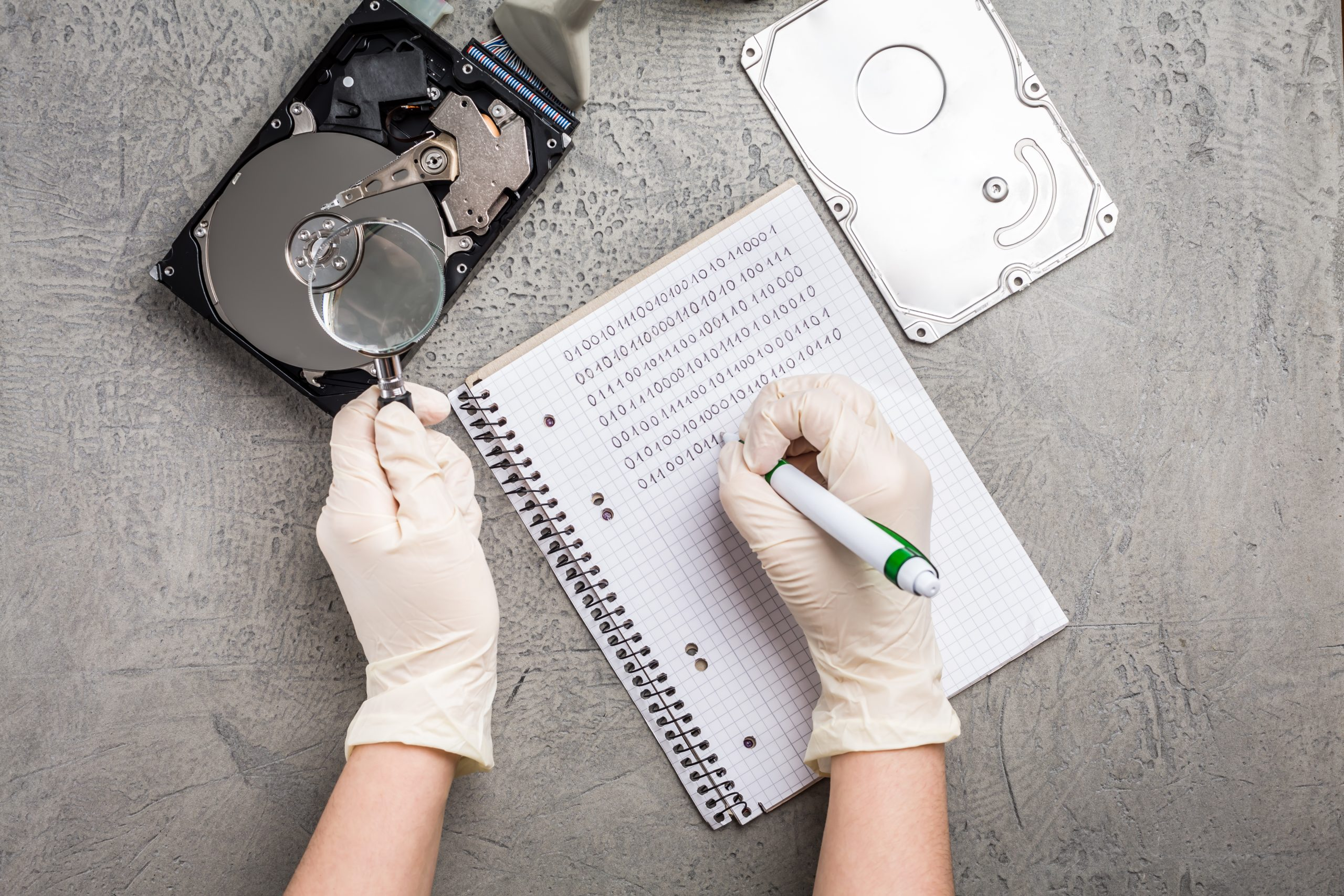 Concept of data recovery, engineer is recovering data from failed hard disk driver. Hdd disk restoration, magnifier and binary code